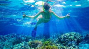 Schnorchlerin im klaren Wasser über bunten Korallen